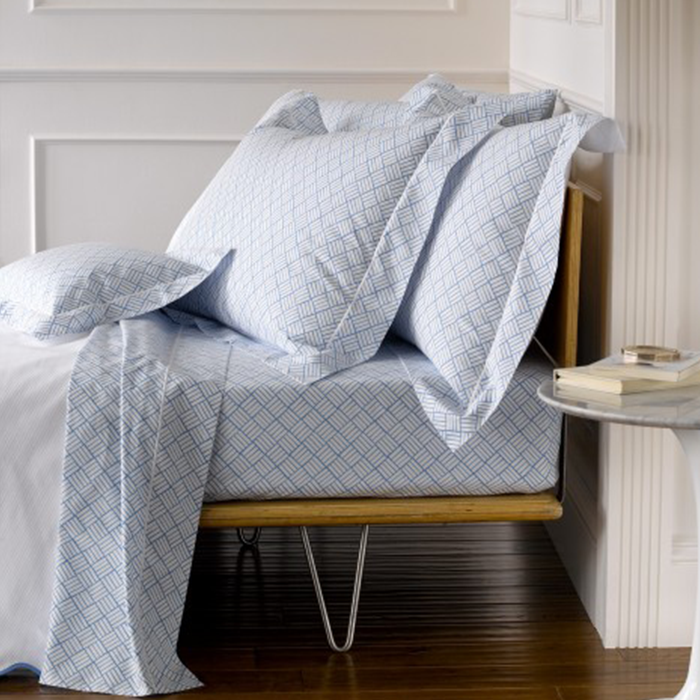 Bed with Blue Patterned Sheet